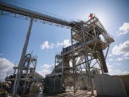 Ouvrier debout sur le criblage de pierre et la machine de concassage dans la carrière — Photo de stock