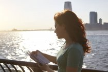 Young female tourist with long red hair looking at guidebook on waterfront, Manhattan, New York, USA — Stock Photo