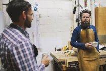 Two craftsmen chatting in pipe organ workshop — Stock Photo