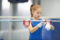 Young gymnast using training wrist straps to aid practise on bars — Stock Photo