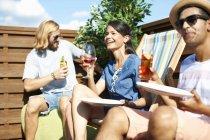 Дорослі друзі сидять на палубних стільцях і п'ють на даху. — стокове фото