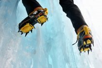 Cropped view of ice climbers feet wearing crampons — Stock Photo