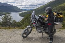 Motorbike rider is checking the map and synchronises it with her GPS in Tierra del Fuego, Argentina — Stock Photo