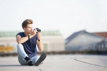 Young man on rooftop, holding camera — Stock Photo