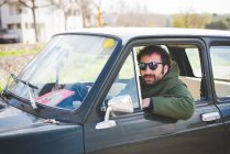Portrait of mid adult man driving vintage car — Stock Photo