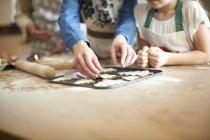 Photo recadrée de femme senior et petites-filles de placer des cookies d'arbre de Noël sur le plateau de cuisson — Photo de stock