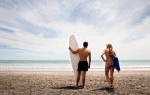 Jovem casal de pé na praia segurando prancha de surf e prancha — Fotografia de Stock