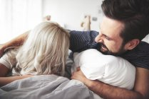 Couple couché sur le lit, homme chatouillant femme — Photo de stock