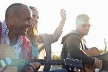 Três amigos tocando violão na praia de Bournemouth, Dorset, Reino Unido — Fotografia de Stock