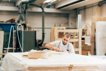 Young adult carpenter at work in workshop — Stock Photo