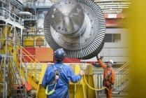 Банкир и оператор крана спускают кран в турбинный зал во время отключения электростанции — стоковое фото