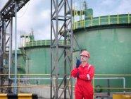 Travailleur tenant la radio, debout devant les réservoirs de stockage de pétrole — Photo de stock