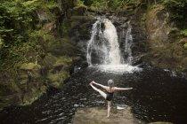 Задній вид зрілої жінки, які практикують йогу перед водоспад — стокове фото