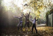 Trois jeunes garçons, jouant à l'extérieur, jetant des lames d'automne — Photo de stock