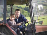 Farmer and young son in tractor in field, portrait — Stock Photo