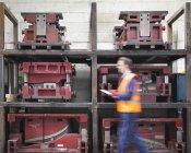 Travailleur avec presse-papiers passant devant les moules dans une usine de tôle — Photo de stock