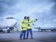 Сотрудники аэропорта в обсуждении на взлетно-посадочной полосе — стоковое фото