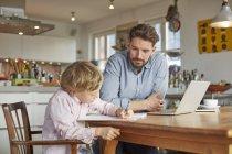 Père aidant fils avec les devoirs au bureau à la maison — Photo de stock
