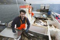 Рибалки gutting риби на човні і, дивлячись на камеру — стокове фото