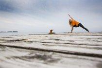 Середині дорослу жінку практики йоги позиції на дерев'яні морський Пірс — стокове фото