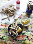 Many whitebait in bowl with lemon salt and beer can — Stock Photo