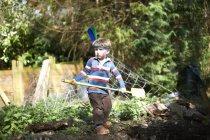 Menino vestindo faixa de cabeça com penas, segurando pá — Fotografia de Stock