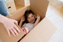 Sonriente chica jugando en caja de cartón - foto de stock