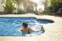 Mature woman swimming in holiday apartment swimming pool — Stock Photo
