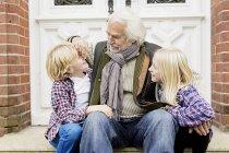 Дедушка сидит с внуками на пороге. — стоковое фото