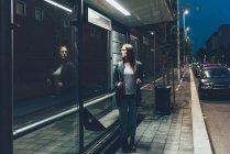 Jeune femme regardant la réflexion dans l'attente à l'arrêt de bus de nuit — Photo de stock