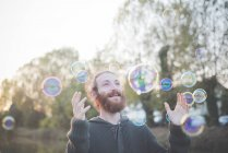 Young man playing with bubbles — Stock Photo
