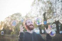 Giovane uomo che gioca con le bolle — Foto stock