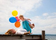 Mother and daughter playing on pier — Stock Photo