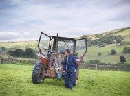 Agriculteur et jeune fils assis sur un tracteur dans le champ — Photo de stock