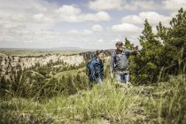 Father pointing out landscape to teenage son on hiking trip, Cody, Wyoming, USA — Stock Photo