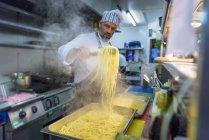 Chef preparing freshly made pasta in traditional Italian restaurant kitchen — Stock Photo