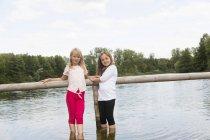 Портрет двух девушек, держащихся за забор во время гребли на сельском озере — стоковое фото