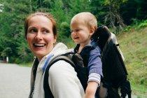 Молода жінка носить сина на вулиці. — стокове фото
