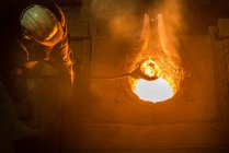 Worker cleaning and preparing surface of molten metal in foundry — Stock Photo