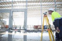 Землемер с помощью штатива и уровня на строительной площадке — стоковое фото