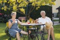 Старший пара, сидячи за столом у саду, насолоджуючись напоєм — стокове фото
