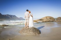 Full length rear view of couple, arms around eachother, standing on rock on coastline — Stock Photo