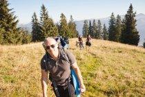 Турист со стаей на травянистом склоне холма — стоковое фото
