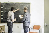Scientists chalking on blackboard in plant growth research facility laboratory — Stock Photo