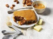 Budino al caramello Sticky su piatto bianco e salsa di caramello caldo in ciotola — Foto stock
