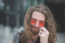 Портрет молодого хиппи в оранжевых солнцезащитных очках и татуированных пальцах — стоковое фото