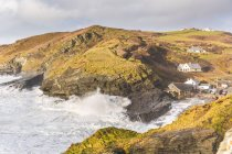 Coastal buildings and ocean waves lapping against cliffs — Stock Photo