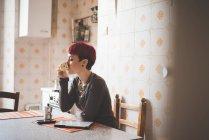Joven mujer sentada en la mesa tomando café - foto de stock