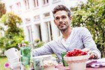 Середині дорослого людини, що сидить за столом в саду — стокове фото