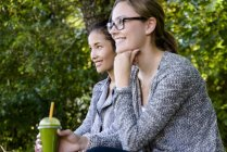 Two young women with takeaway coffee sitting in park — Stock Photo